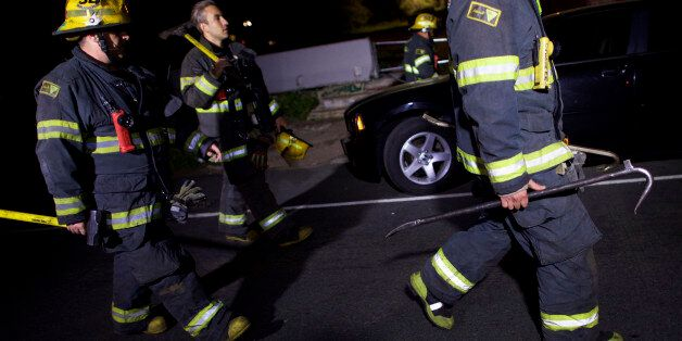 PHILADELPHIA, PA - MAY 13: Fire fighters carry tools back to their truck in the early hours after working...