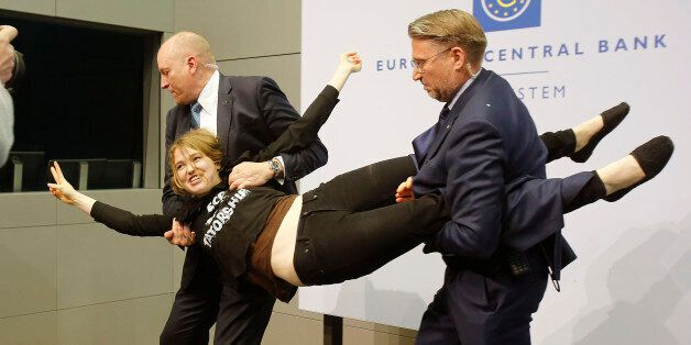 A Femen activist is carried away after attacking ECB President Mario Draghi during a press conference...