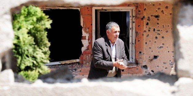 A man walks through a destroyed house in Kumanovo on May 12, 2015. Special police units pulled out of...