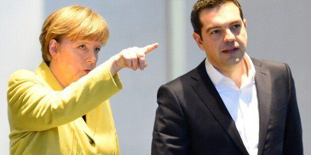 German Chancellor Angela Merkel (L) and Greek Prime Minister Alexis Tsipras arrive to address a press...