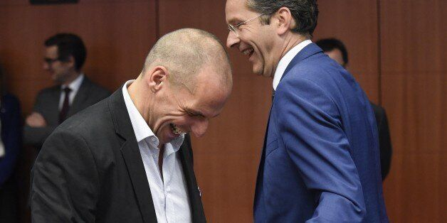 Greek Finance Minister Yanis Varoufakis (L) jokes with Dutch Finance Minister and president of Eurogroup...