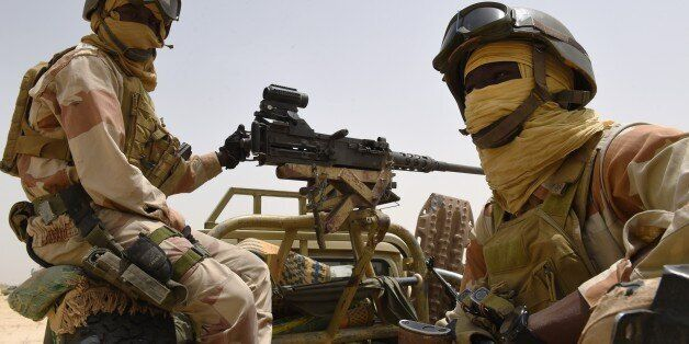 Nigerien army forces sit in the back of an armed pickup truck at their base near Malam Fatori on April...
