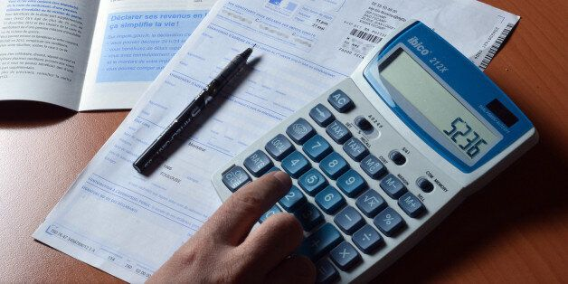 A person uses a calculator as he fills out a pre-filled tax declaration for the 2012 income tax on March...