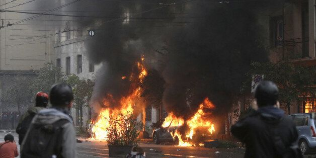Black smoke billows from a burning car as clashes broke out between demonstrators and police during a...