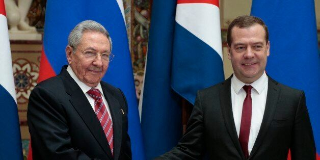 Russian Prime Minister Dmitry Medvedev, right, and Cuban President Raul Castro shake hands at their meeting...