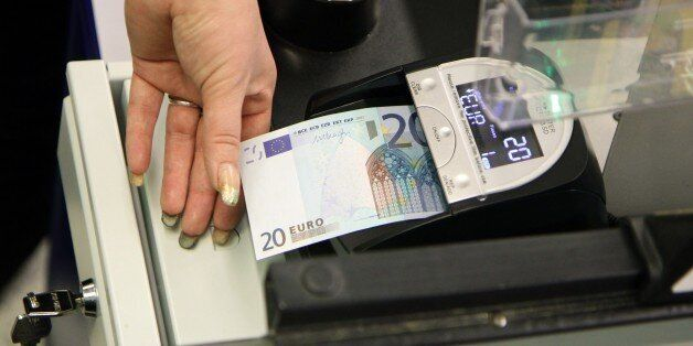 A cashier inspects a euro banknote in a supermarket in Vilnius on January 1, 2015. Lithuania switched...