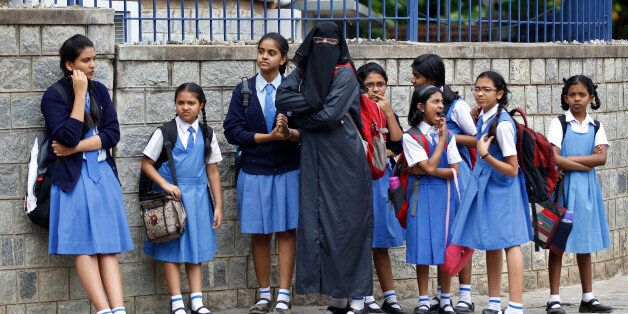 A veiled Muslim school girl stands with fellow students at the end of the day outside a school in Bangalore,...