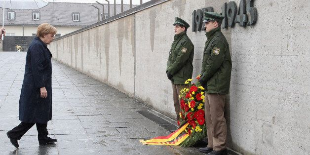 DACHAU, GERMANY - MAY 03: German Chancellor Angela Merkel lays down a wreath to commemorate the 70th...