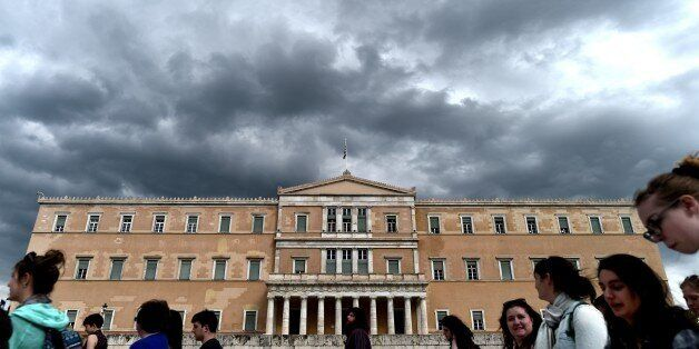 People walk in front of the Greek Parliament in Athens on April 7, 2015. Greek lawmakers voted on April...