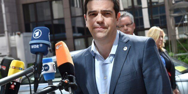 Greece's Prime minister Alexis Tsipras addresses reporters upon his arrival at the European Council headquarters...