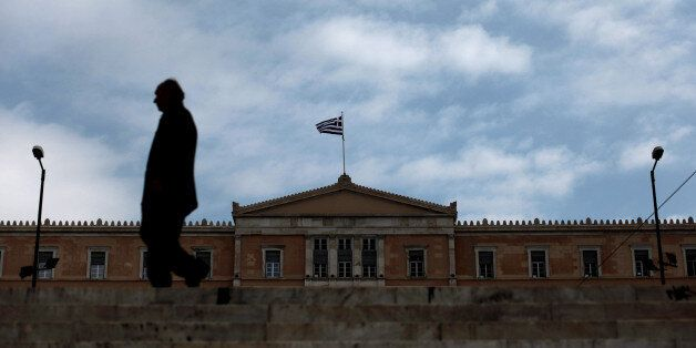 A man walks in front of the Greek Parliament in Athens on November 27, 2012. The eurozone and IMF saved...