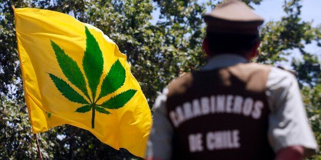 A police officer observes a march calling to legalize the medicinal use of cannabis in Santiago, Chile,...