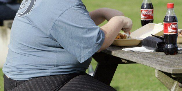 FILE- In this file photo dated Wednesday, Oct. 17, 2007, an overweight person eats in London, Wednesday,...