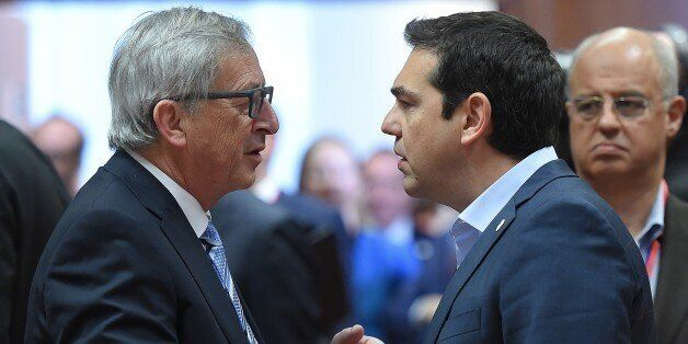 European Commission President Jean-Claude Juncker (L) speaks with Greek Prime Minister Alexis Tsipras...
