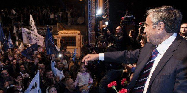 Turkish-Cypriot presidential candidate Mustafa Akinci (R) throws flowers to supporters during a campaign...