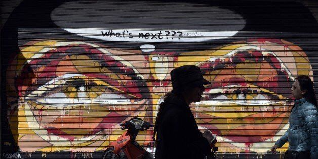 Women walk past shut down store with graffiti on it in central Athens on March 30, 2015. Cash-strapped...