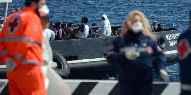 An italian tugboat carrying immigrants arrives on April 15, 2015 in the Italian port of Messina in Sicily....