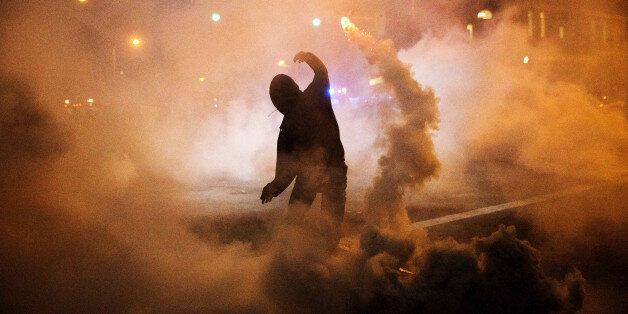 A protester throws a tear gas canister back toward riot police after a 10 p.m. curfew went into effect...