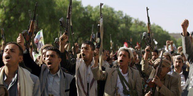Tribal gunmen loyal to the Shiite Huthi movement raise their weapons on April 16, 2015 in the capital...