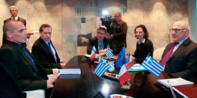Greek finance minister Yanis Varoufakis, left, speaks with his French counterpart Michel Sapin, right,...