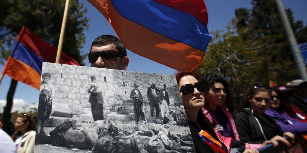 Members of the Armenian community hold the Armenian flags and placards during a demonstration on April...