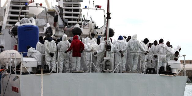 Migrants wait to disembark from an Italian Coast Guard ship after being rescued in Porto Empedocle, Sicily,...
