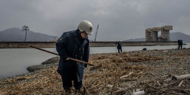 RIKUZENTAKATA, JAPAN - MARCH 11: A police officer searches the shoreline for the remains of tsunami victims...