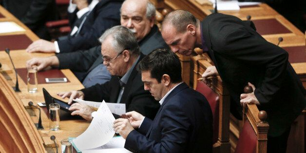Greek Minister Alexis Tsipras front and his Finance Minister Yanis Varoufakis, right, look on papers...