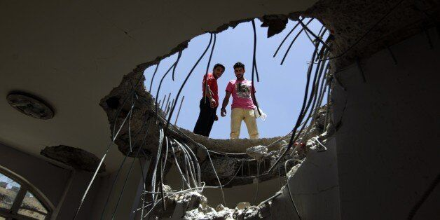Yemenis look down through a hole in the roof of a house which was damaged the day before during an air...