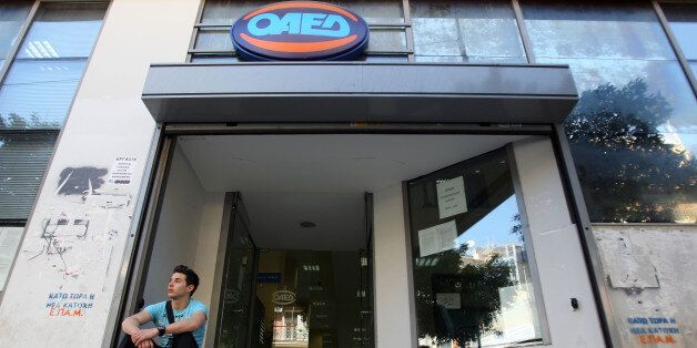 A young man waits outside Labor Force Employment Organization (OAED) in Athens, Thursday, April 11, 2013....