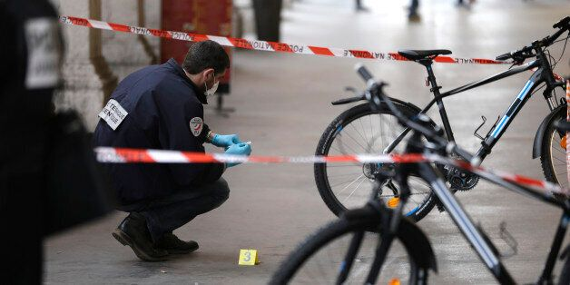 A police officer collects clues after an attacker with a knife hidden in his bag attacked three soldiers...