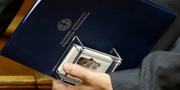 Greece's Finance Minister Gikas Hardouvelis, holds a clear case with two flash drives containing the...