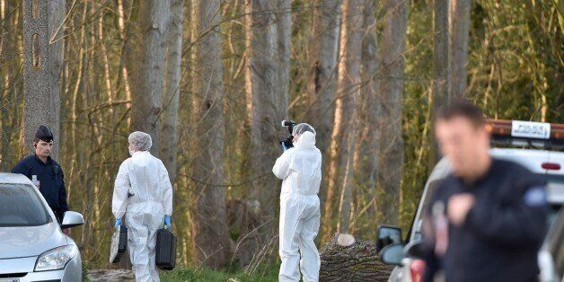 Forensics experts take photos near the site in the Dubrulle forest where the dead body of an 8-year-old...