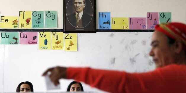 A Turkish Cypriot woman casts her vote in front of a portrait of Mustafa Kemal Ataturk, the founder of...