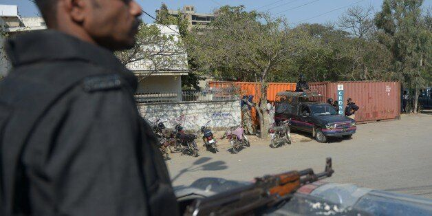 Pakistani policemen stand guard outside the French consulate following protests there against the printing...