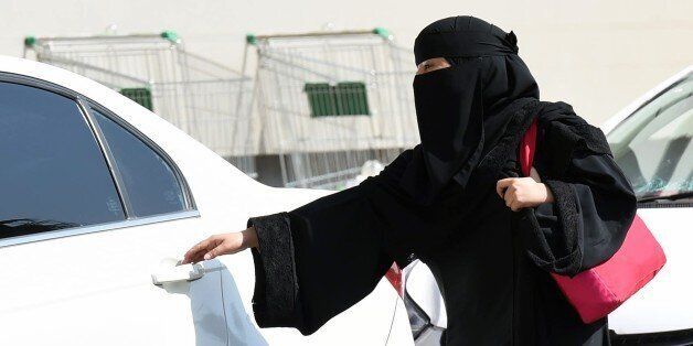 A Saudi woman gets into a taxi at a mall in Riyadh as a grassroots campaign planned to call for an end...