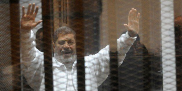 Egypt's deposed Islamist president Mohamed Morsi waves from inside the defendants cage during his trial...