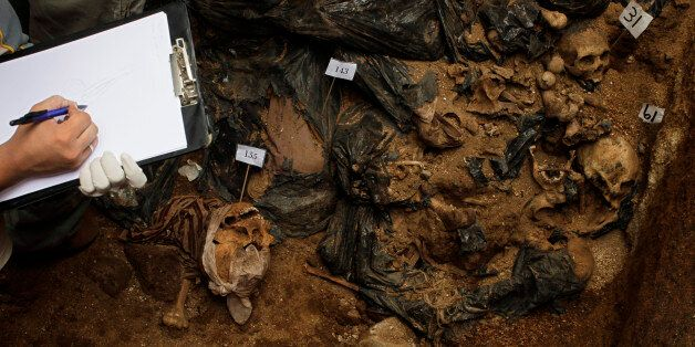 A forensic takes notes at a mass grave found during renovation works at a public school in Mixco, in...