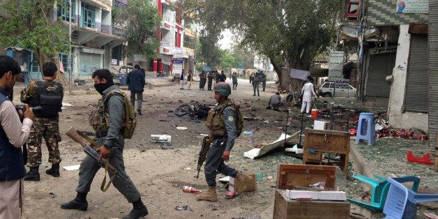 Afghan security forces members inspect the site of a suicide attack near a new Kabul Bank in Jalalabad,...
