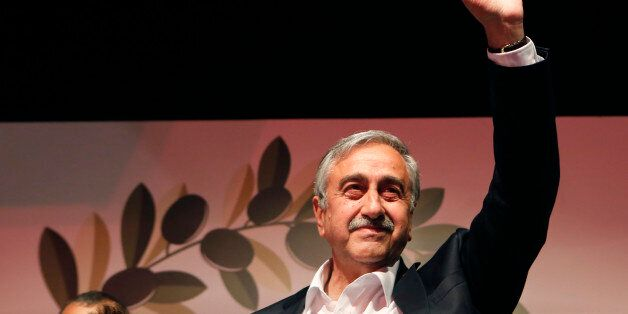 Turkish Cypriot newly elected leader Mustafa Akinci waves to his supporters after won the leadership...