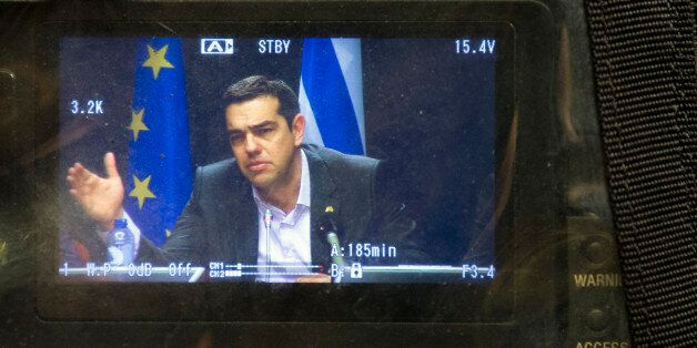 Greek Prime Minister Alexis Tsipras appears on a television monitor as he speaks during a press conference...