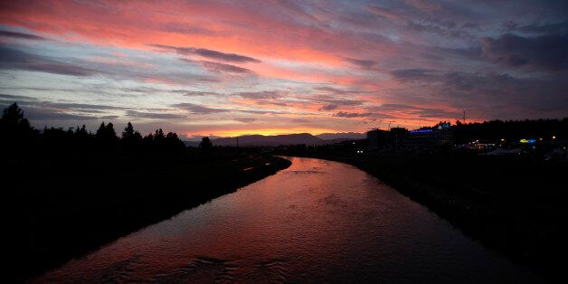 The sky, red from the sunset, casts its reflection in Vardar River in Skopje, Macedonia, after a heavy...