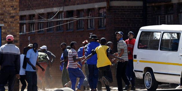 Local residents run away as police fired rubber bullets and teargas to disperse a crowd of anti-immigrant...