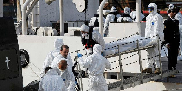 Italian Coast Guard officers disembark the body of a dead migrant off the ship Bruno Gregoretti, in Valletta's...
