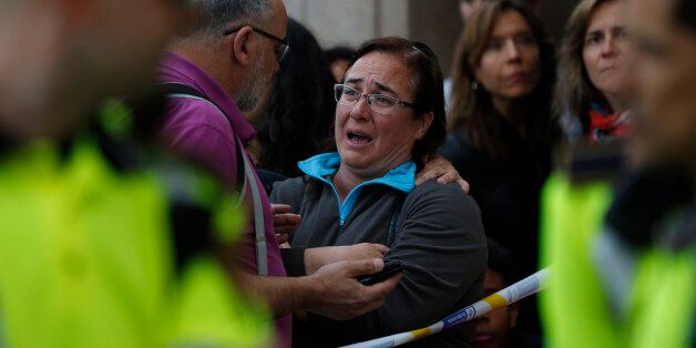 People stand outside a high school in Barcelona, Spain, Monday, April 20, 2015, where a minor has been...