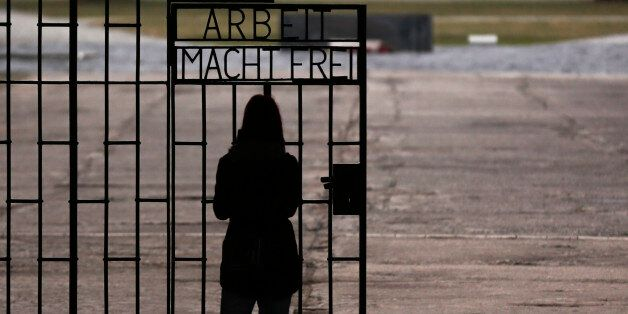 A woman stands in front of the gate of the Sachsenhausen Nazi death camp with the phrase 'Arbeit macht...