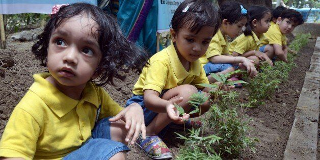 Young Indian schoolchildren participate in a tree planting programme on the occasion of Earth Day in...
