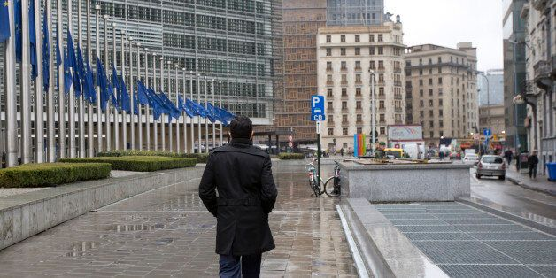 A man walks by EU flags at half-staff in front of EU headquarters in Brussels on Wednesday, March 25,...