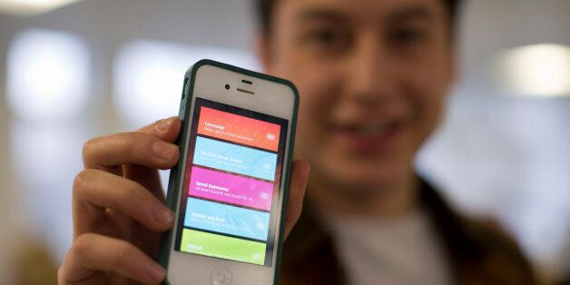Nick d'Aloisio displays his mobile application Summly, as he poses for photographs after being interviewed...