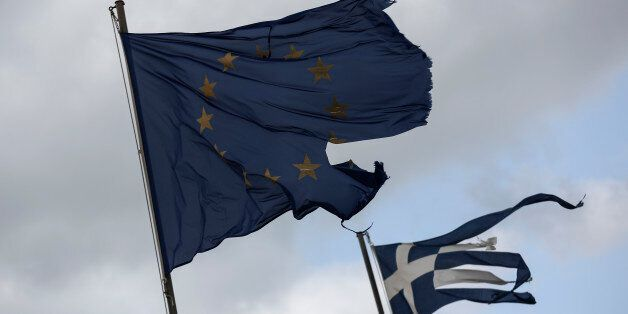 Ruined EU and Greek flags fly in tatters from a flag pole at a beach at Anavissos village, southwest...